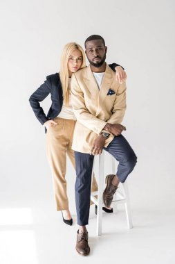 full length view of fashionable beautiful multiethnic couple looking at camera on grey