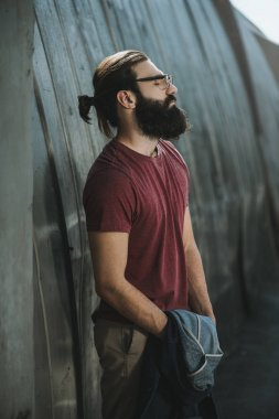 Handsome bearded man posing near old hangar stock vector