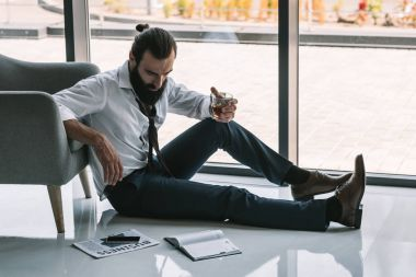 drunk businessman sitting on floor