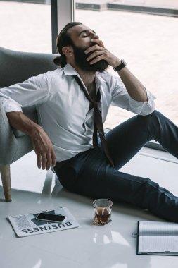 drunk businessman sitting on floor