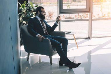 serious businessman using smartphone