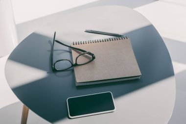 smartphone, notepad and eyeglasses