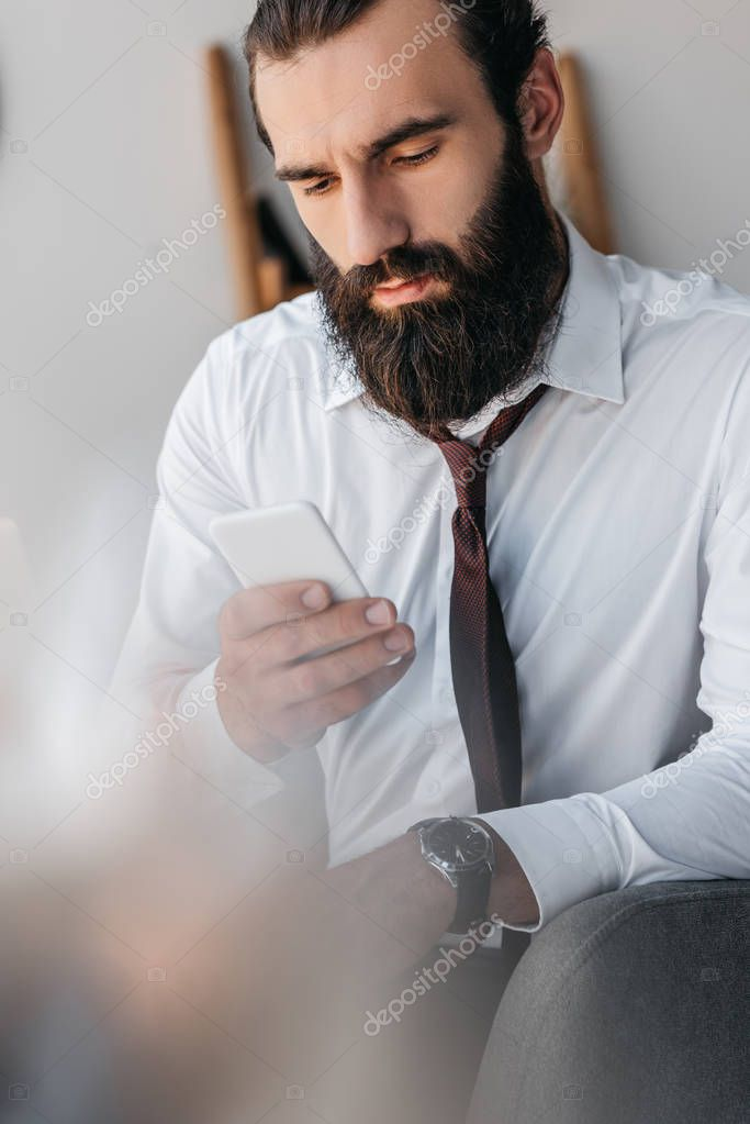 bearded businessman using smartphone