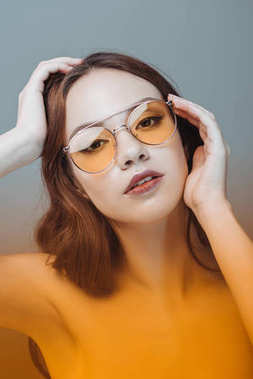sensual girl posing in yellow sunglasses, isolated on grey