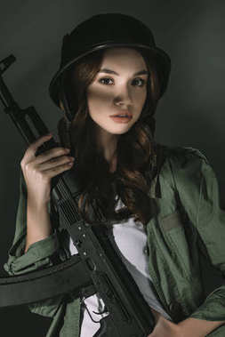 beautiful caucasian young girl in military helmet with rifle, on grey with shadows