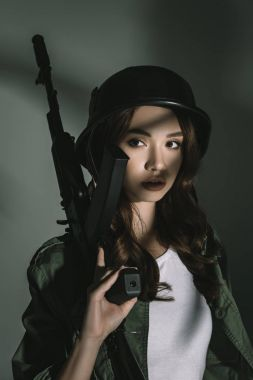 beautiful girl posing in military helmet with rifle, on grey with shadows