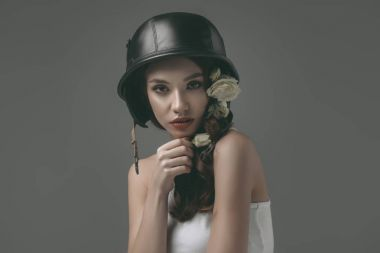 beautiful young girl in military helmet with white flowers, isolated on grey