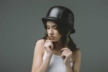 attractive young girl in military helmet, isolated on grey