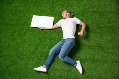 man with blank placard on grass