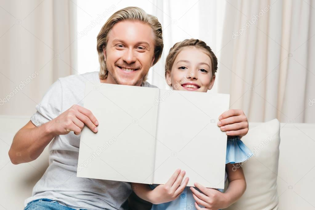 father and daughter holding book