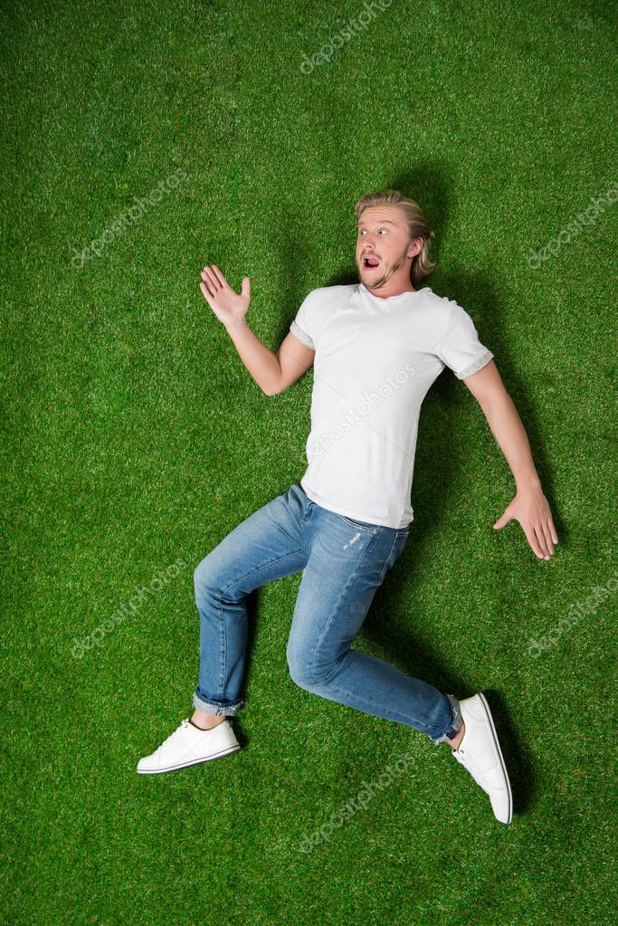 man lying in funny position on grass