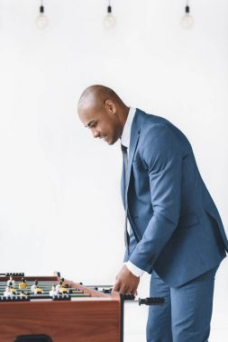 Businessman playing table football