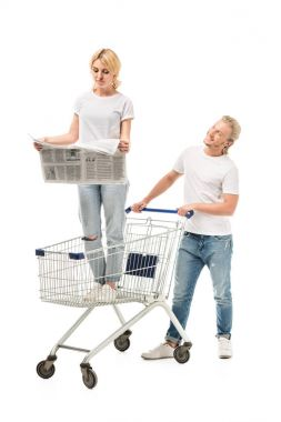 Woman reading newspaper in shopping cart while man standing near by isolated on white stock vector