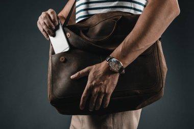 man putting smartphone into bag