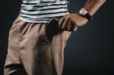 man putting smartphone into pocket