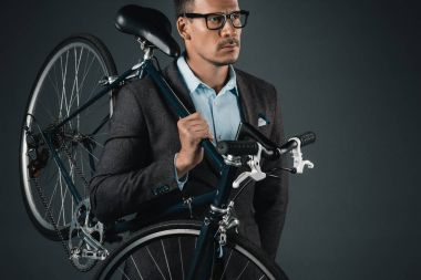 businessman in formal wear holding bicycle