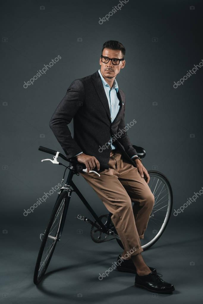 young stylish businessman sitting on bicycle