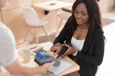 woman paying with credit in cafe