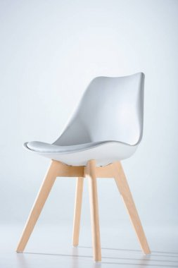 Studio shot of stylish chair with white top and light wooden legs standing on white stock vector