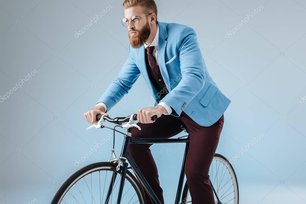 fashionable man in suit on bicycle