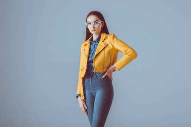 Portrait of stylish woman standing akimbo in leather jacket and eyeglasses isolated on blue stock vector