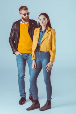 Fashionable couple in leather jackets and jeans isolated on blue stock vector