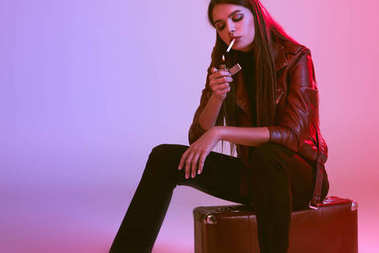smoking girl sitting on suitcase