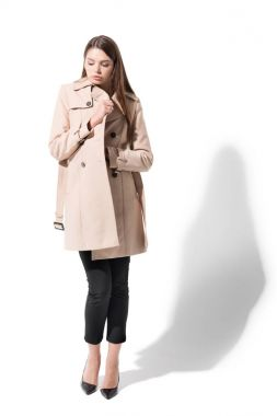 Attractive girl posing in classic trench coat, on white stock vector