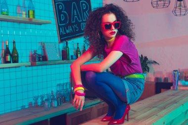 stylish woman sitting on counter