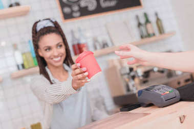 barista giving customer coffee