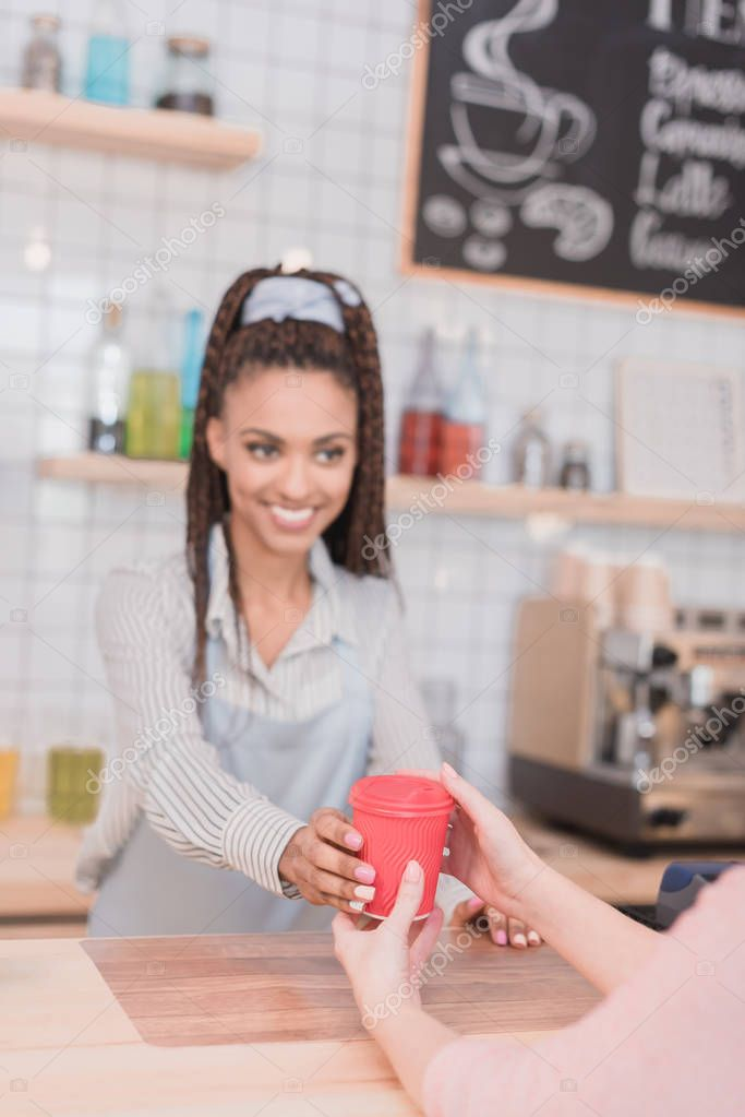 barista handing customer coffee