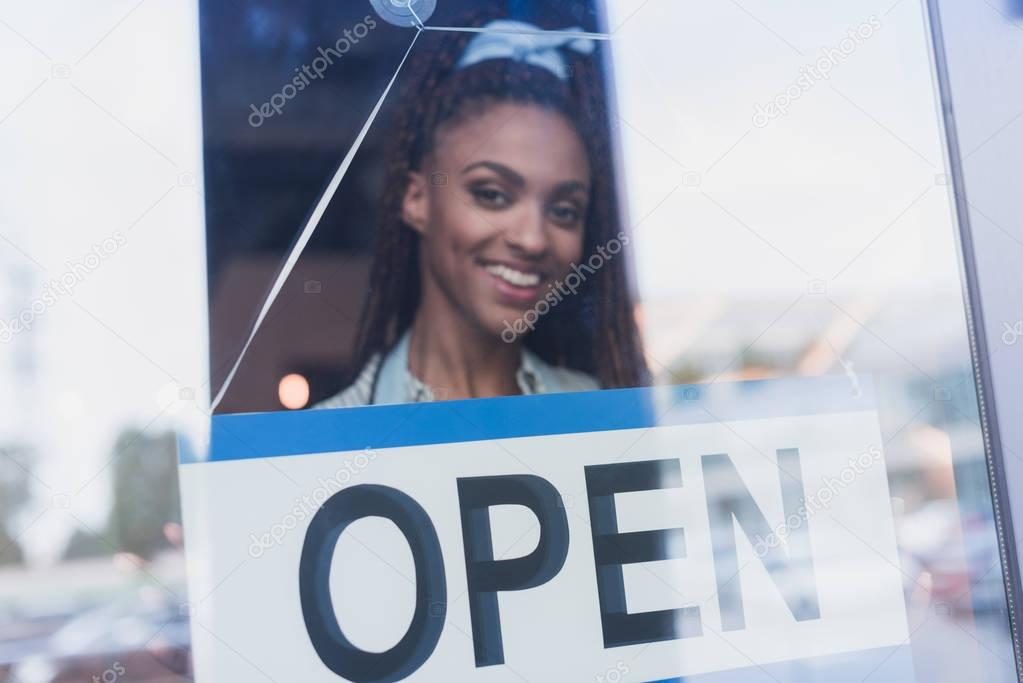 Employee hanging open sign on door