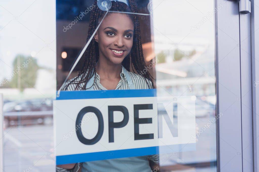 Employee hanging open sign on door