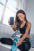 Fotografie sportliche Frau zeigt smartphone