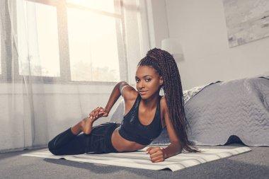 woman stretching leg on yoga mat