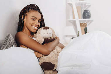 Woman with teddy bear in bed