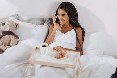 Woman with breakfast in bed and talking by phone