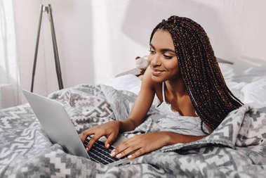 Beautiful african american woman using laptop in bed at morning stock vector