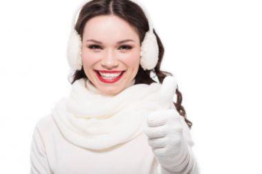 Woman in earmuffs showing thumb up