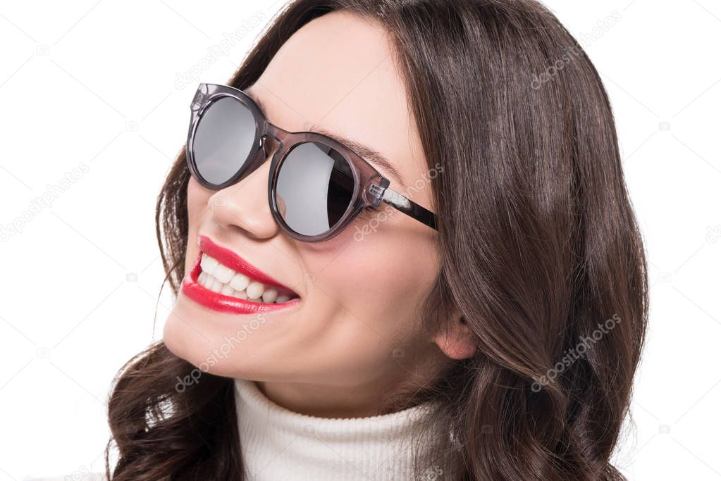 Portrait of young smiling woman with bright makeup wearing trendy sunglasses, isolated on white