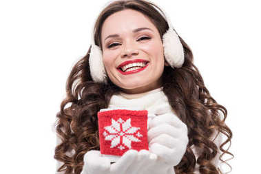 woman in winter earmuffs holding cup