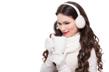 woman in winter earmuffs drinking from mug