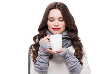 woman in warm clothes smelling coffee