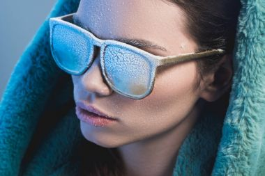 woman with frost on face wearing sunglasses