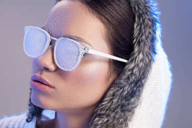 Trendy woman in sunglasses covered in frost