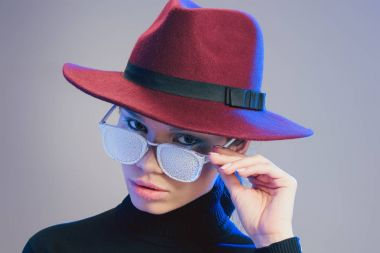 Young good-looking woman wearing wide-brimmed hat, looking at camera over sunglasses covered in frost stock vector