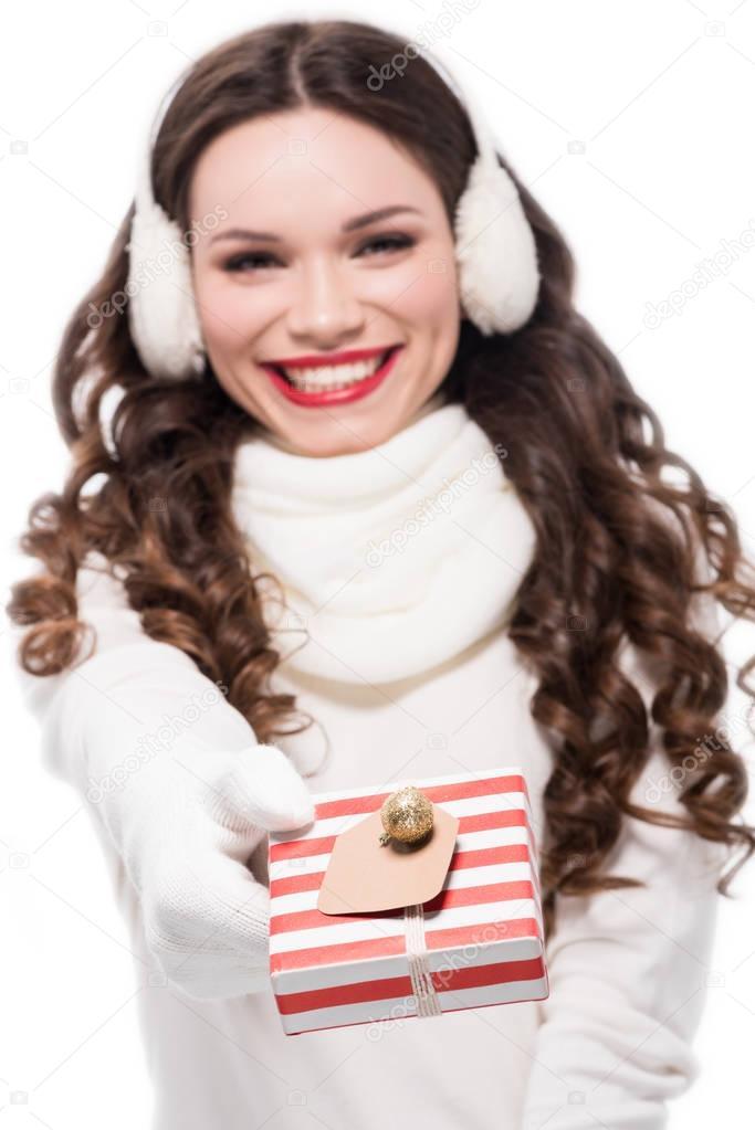 woman in winter earmuffs holding gift