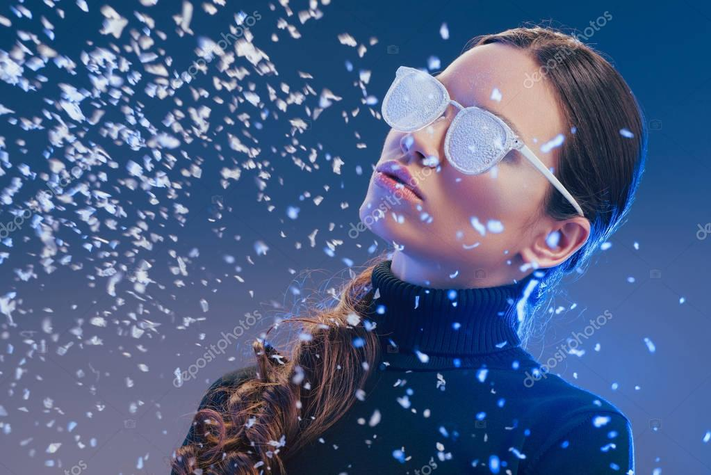 Woman in sunglasses standing in snow