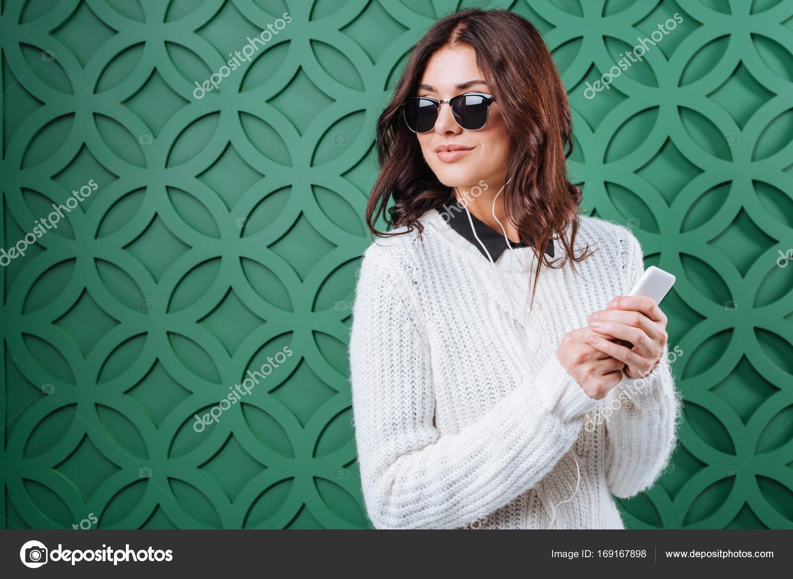 079f35ff5db54 Mulher elegante na camisola de inverno branco e óculos de sol pretos  ouvindo música com smartphone em verde — Foto de VitalikRadko