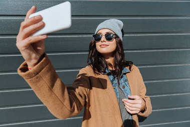 Woman in autumn outfit taking selfie